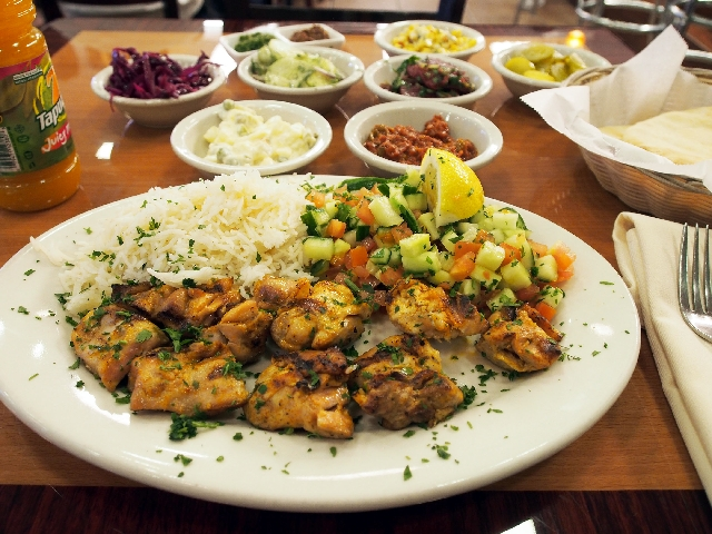 Jerusalem Grill serves grilled chicken, rice and Israeli salad with, bottom from left, Israeli potato salad, matbucha and pita bread; center, red cabbage, Israeli cucumber salad, Moroccan-style be ...
