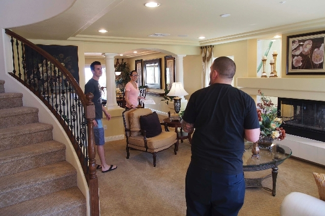 Eric Wennerberg, left, and his sister Emily talk with their friend John Siemer as they tour a model home in April in the Coronado Ranch subdivision in Las Vegas. U.S. new-home sales rose in April  ...