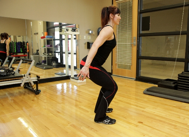 Position the feet hip width apart. Contract the core and straighten the back.