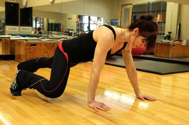 Begin in a pushup position. Bring one foot up to the hip and position it outside of shoulder width. Move the opposite hand forward about a hand's length. Contract the core.