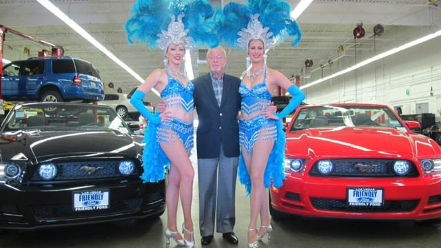 Ed Olliges, chairman of Friendly Ford, welcomes two showgirls clad in Ford blue costumes, during the dealership's 43rd anniversary celebration.