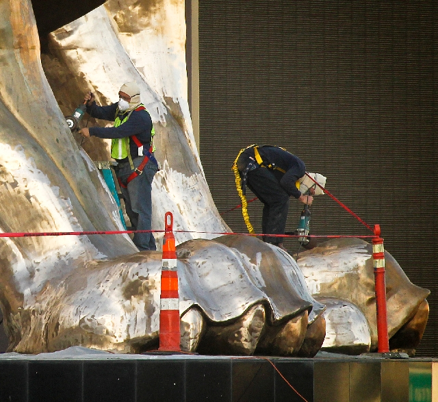Workers polish the paws of the lion statue in front of the MGM Grand on Wednesday, the day before the resort's parent company unveiled its first profitable quarterly earnings since 2008.