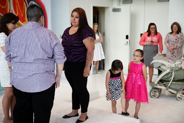 Melissa Molina, third from left, cries during a ceremony with her partner Tracy Molina, second from left, at the Pop-Up Wedding Chapel on Thursday,. Their young children Miley Alonzo-Molina, left, ...