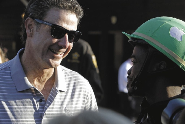 Part-owner of Kentucky Derby hopeful Goldencents Rick Pitino, left, talks to jockey Kevin Krigger at Churchill Downs Wednesday.
