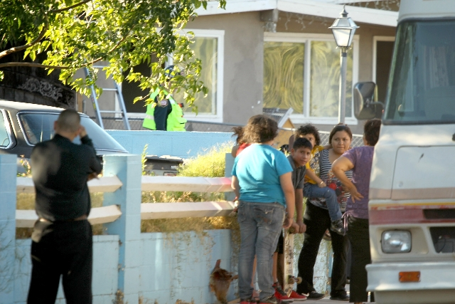 People gather near the house  fire at  the corner of Weeping Willow Avenue and Howard Drive in Las Vegas on Thursday. Police and fire officials  are ruling a blaze that killed a young boy and inju ...