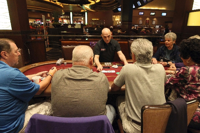 Dealer Joe Molinario, center, wears an Ultimate Poker shirt Friday in the poker room at Red Rock Resort. Ultimate Poker has registered thousands of users from every U.S. state and 20 different cou ...