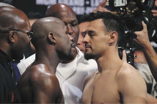 Boxers Floyd Mayweather Jr., left, and Robert Guerrero face off during the official weigh in for their fight at the MGM Grand Garden Arena in Las Vegas on Friday.