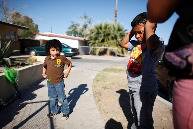 Eight-year-old Danny Funes, right, and 5-year-old brother Steven Funes look at a memorial Friday for 7-year-old Jacob West, who was killed in a house fire on Thursday.