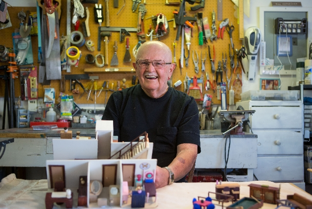 Bill Hornecker shows off pieces from miniature houses he has constructed in his home workshop