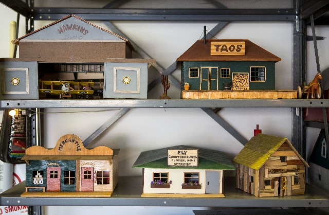 Bill Hornecker displays minature homes in his home workshop.