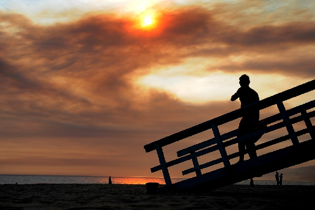 As smoke billows from wildfires, a lifeguard keeps an eye on swimmers at Zuma Beach on Friday in Malibu, Calif. A huge Southern California wildfire burned through coastal wilderness to the beach o ...
