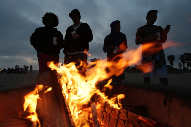 Beach goers stand around a fire pit  in Huntington Beach, Calif. Air quality regulators are considering a proposal to ban beach bonfires in Southern California due to health concerns.
