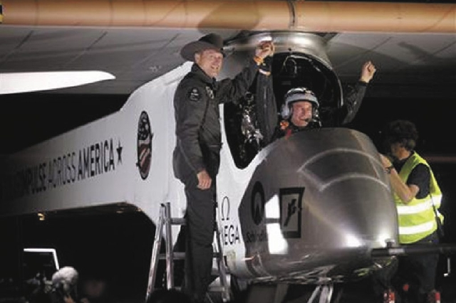 Solar Impulse co-founder, pilot and CEO Andre Borschberg, left, greets pilot Bertrand Piccard at Sky Harbor International Airport in Phoenix, early Saturday, after completing the first leg of its  ...
