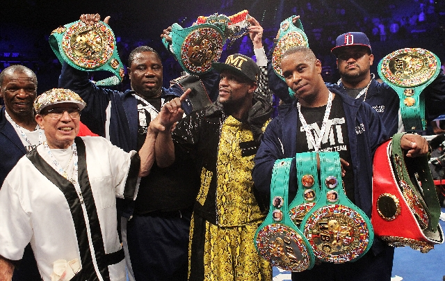 Floyd Mayweather Jr., center, poses with his championship belts and entourage Saturday after retaining his WBC welterweight title by beating Robert Guerrero by unanimous decision at the MGM Grand  ...