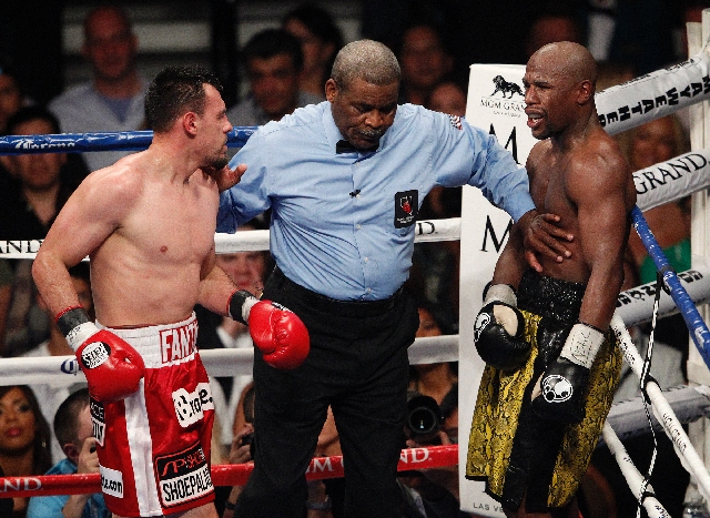 Referee Robert Byrd separates Floyd Mayweather, right, and Robert Guerrero in their WBC Welterweight Title bout at the MGM Grand in Las Vegas Saturday