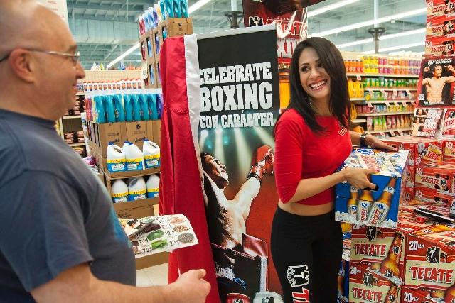 Tecate promoter Marisela Rebollar hands over a case of beer to Mario Giglioli of Las Vegas at a Marketon supermarket.