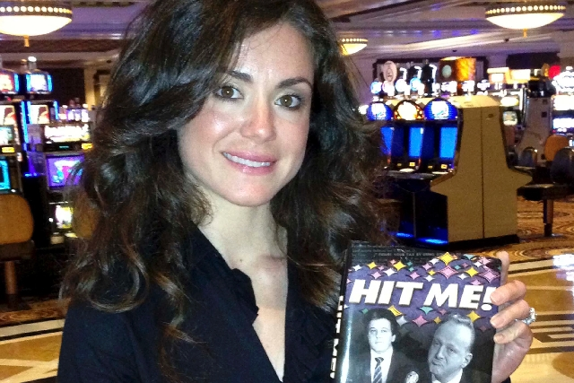 """Danielle Gomes is shown with her book """"Hit Me!"""" at Caesars Atlantic City on April 25. The book is about her father, the late gaming industry executive and Gaming Control Board official Dennis Gomes."""