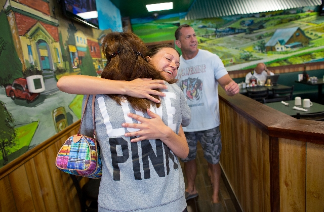 Sarah Gehringer, general manager at the Egg & I, hugs a customer during the reopening of the restaurant on Monday.