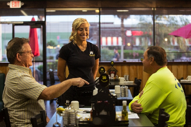 Egg & I server Thaynara Martins, center, waits on customers Randall Vincent, left, and Ed Vargas during the reopening of the restaurant at 4533 W. Sahara Ave.  on Monday. The restaurant reopened f ...