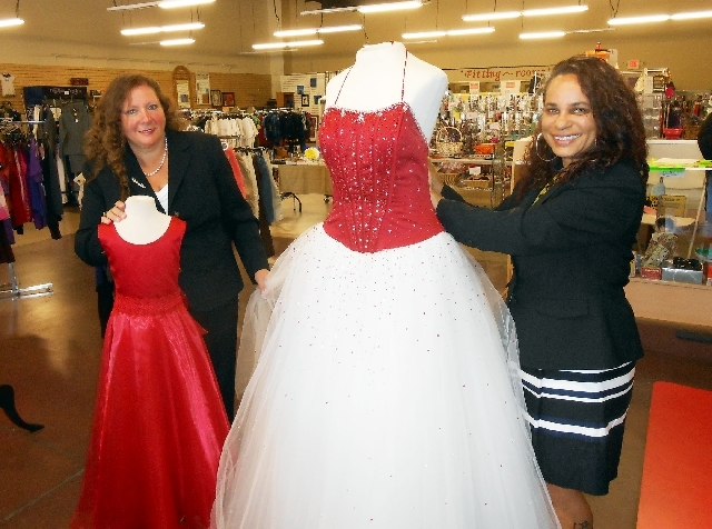Michele Morgan-Devore, left, executive director of Dinosaurs & Roses, puts the finishing touches on a child's ball gown May 3, while Qury Edmond, owner of New 2 U, 921 W. Owens Ave., straightens a ...