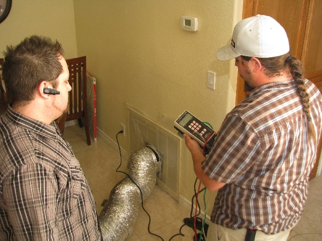 Drew Levy, left, and Dustin Terry of Innovative Energy Solutions inspect a Henderson homeowner's ventilation system.