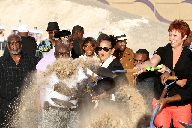 Community leaders and officials toss dirt during a groundbreaking ceremony for the F Street reopening project in historic West Las Vegas on Monday.