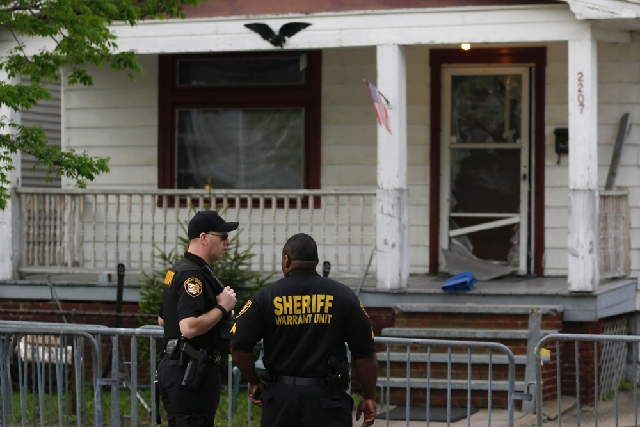 Sheriff deputies stand outside a house in Cleveland on Tuesday, the day after three women who vanished a decade ago were found there. Amanda Berry, Gina DeJesus and Michelle Knight, who went missi ...