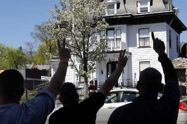 Protesters gesture outside the Graham, Putnam, and Mahoney Funeral Parlors in Worcester, Mass., on Monday, where the body of killed Boston Marathon bombing suspect Tamerlan Tsarnaev is being prepa ...