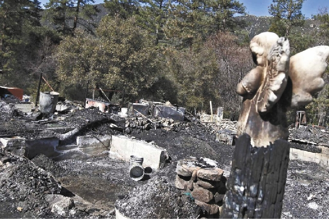 The burned-out cabin where Christopher Dorner's remains were found is seen Friday Feb. 15, 2013 after a police standoff Tuesday near Big Bear, Calif.  The basement area, lower left, is where Dorme ...
