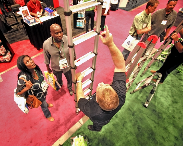David Ondich demonstrates Telesteps Ladders to Las Vegans Bernice Ohene, right, and Cheikh Beye on Tuesday at the National Hardware Show. Among the industry-only attendees at the show are Home Dep ...
