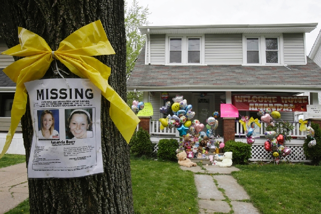 A missing poster still rests on a tree outside the home of Amanda Berry Wednesday in Cleveland. Berry, 27, Michelle Knight, 32, and Gina DeJesus  had apparently been held captive in a house since  ...