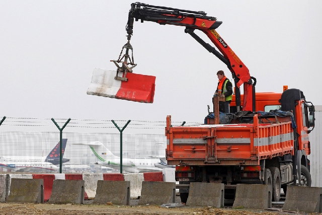 In this Feb. 19 file photo, workers place concrete blocks to block access to a security fence next to the tarmac at Brussels international airport. Police carried out a series of raids on Wednesda ...