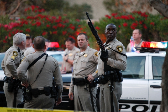 Las Vegas police gather at an apartment complex at the corner of Washington Avenue and Watkins Drive near the scene of a shooting in Las Vegas Wednesday.