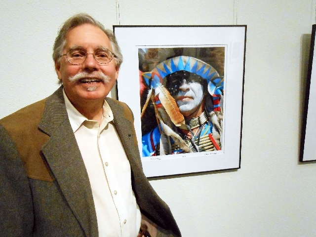 """Lamar Marchese stands by one of his favorite photos, titled """"Buffalo Man,"""" at his """"Pow Wow Portraits"""" exhibit that opened May 7 at the Rainbow Library."""