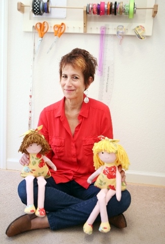 Diane Eugster sits in her home studio, where she creates and sews her eco-friendly rag dolls.