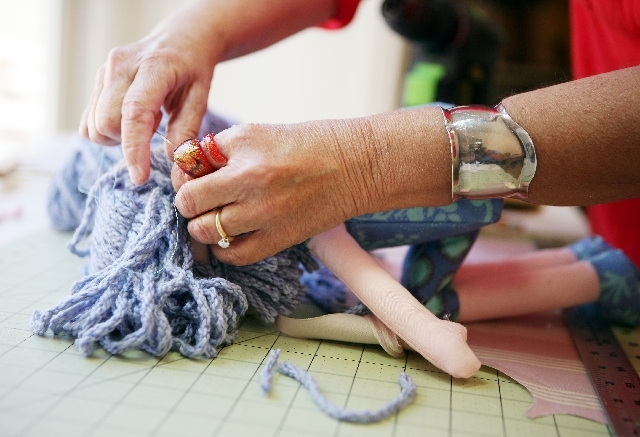 Diane Eugster sews yarn for hair onto a doll in her home studio in The Lakes area, May 10. Her dolls, called Rag Dolls Rising, are sold locally and internationally online at etsy.com. Each is uniq ...