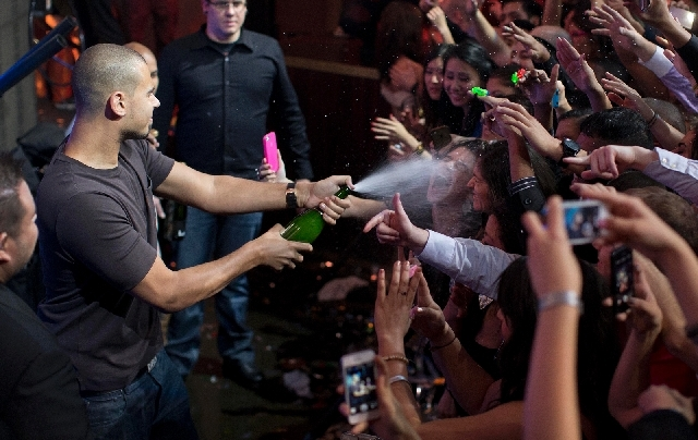DJ Afrojack sprays revelers with Champagne while performing at XS nightclub, where he'll be spinning at the opening of night swim on Sunday.
