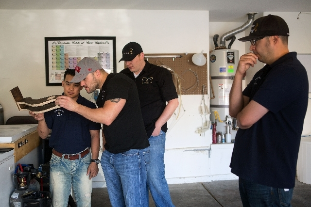 From left, Eddy Quiogue, Marc Longwith, Michael Beaman and Roberto Mendosa look over a prototype of a beer sampler tray inside Longwith's garage May 13. Their company Banger Brewing is scheduled t ...