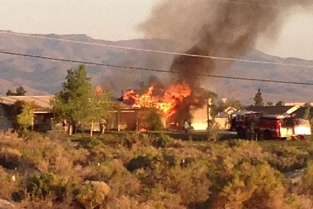 A married couple was found dead on Monday in this Fernley home about 30 miles east of Reno. Neighbor Michael Bergman snapped a cell phone photo when he saw the home on fire.