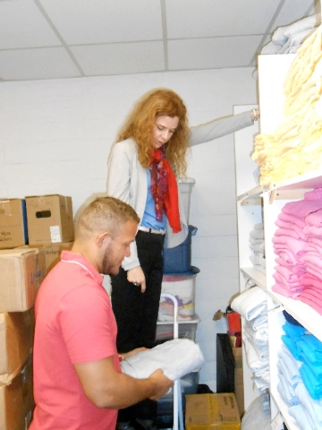 Daniele Dreitzer, executive director of the Rape Crisis Center, and staff member Peter Guevara unpack and sort clothing for victims of sexual assault.