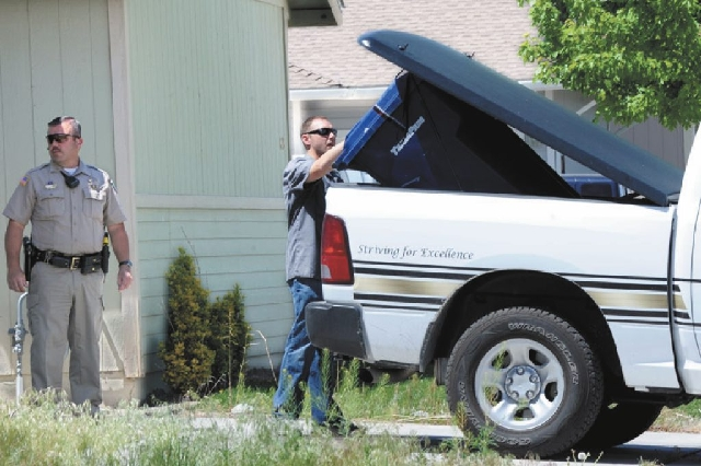 A sealed garbage container is loaded into the back of a Lyon County Sheriff's vehicle Tuesday in Fernley.