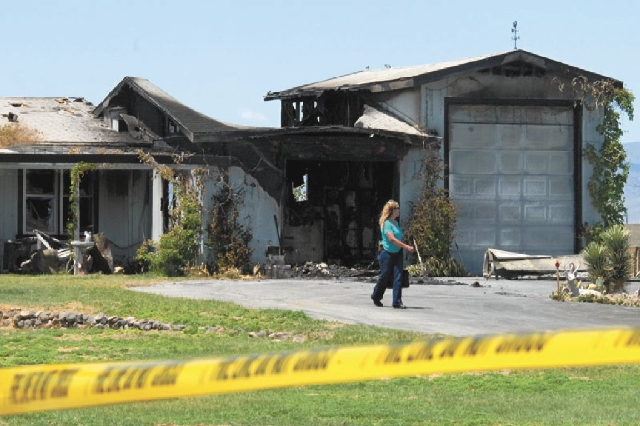 An investigator leaves the scene Tuesday of a double homicide at 975 Jessica in Fernley. The house was set on fire. Four people were killed Monday in the Northern Nevada town near Reno. Another bo ...