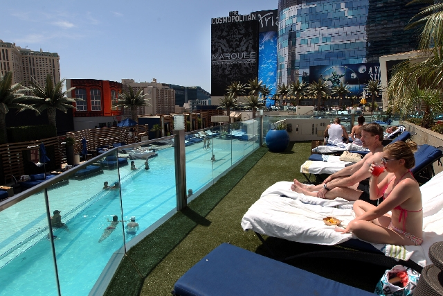 Courtney Anderson, right, sips her drink as she and her friend Eric Rust, both of Seattle, enjoy sunbathing by the pool Wednesday at The Cosmopolitan of Las Vegas on the Strip.