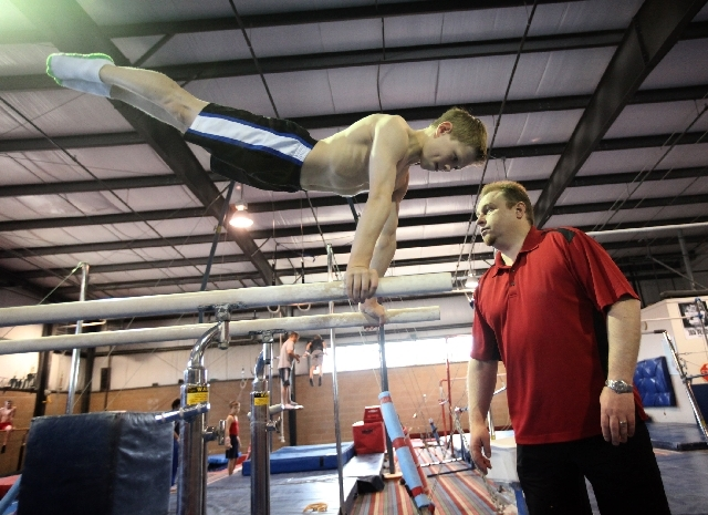 Vitaly Scherbo watches Nikita Bolotsky work out Wednesday at the Vitaly Scherbo School of Gymnastics. Scherbo has operated his school since 1997, and Bolotsky is his first national champion. Scher ...