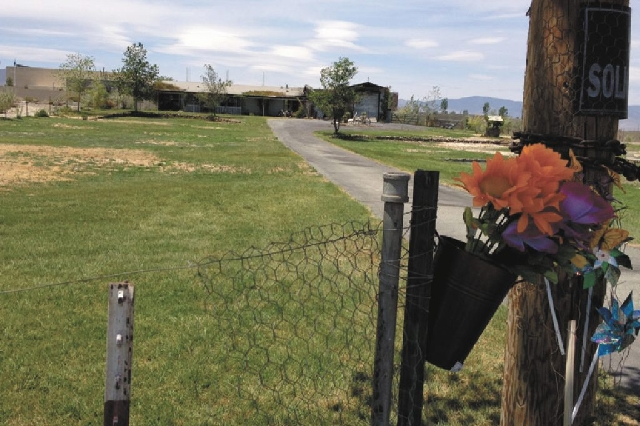Flowers and pinwheels are attached to a fence Wednesday in front of the burned-out house at 975 Jessica in Fernley, the scene a double homicide on Monday.