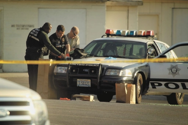 Las Vegas police collect evidence Thursday morning in a parking lot near East Charleston and Bruce Street. Police shot and wounded a man they say was brandishing a pellet gun about 1:30 a.m. The s ...