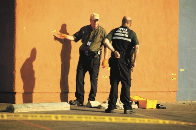 Las Vegas police analyze bullet holes Thursday morning on the outside wall of a building near the intersection of East Charleston and Bruce Street. An officer shot and wounded a man they say was b ...