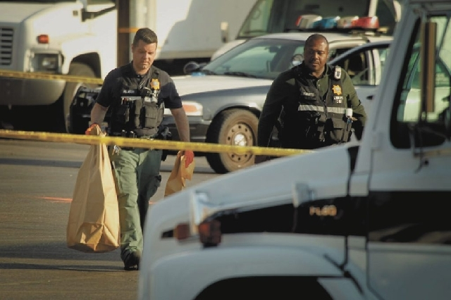 Las Vegas police collect evidence Thursday morning near the intersection of East Charleston and Bruce Street after an officer-involved shooting about 1:30 a.m. Police shot and wounded a man they s ...