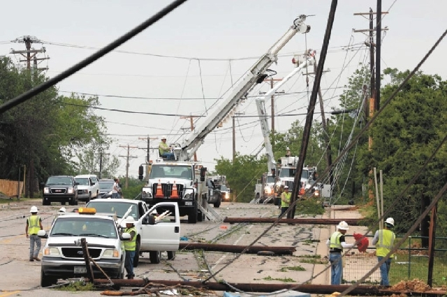 Utility workers try to restore electric power on down lines Thursday in Cleburne, Texas. A rash of tornadoes slammed into several small communities in North Texas overnight, leaving at least six p ...