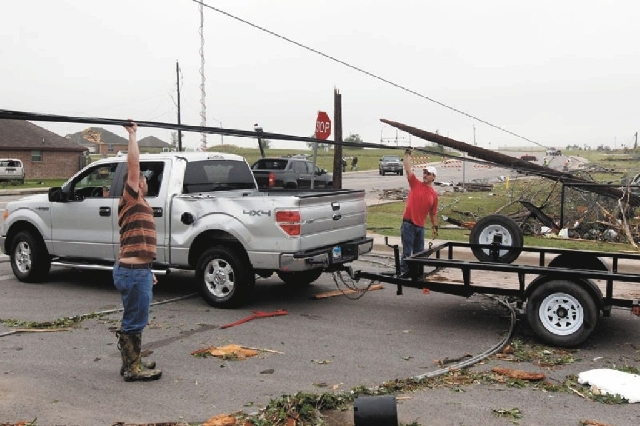 Residents raise a downed power lines to help a motorist Thursday in Cleburne, Texas. A rash of tornadoes slammed into several small communities in North Texas overnight, leaving at least six peopl ...